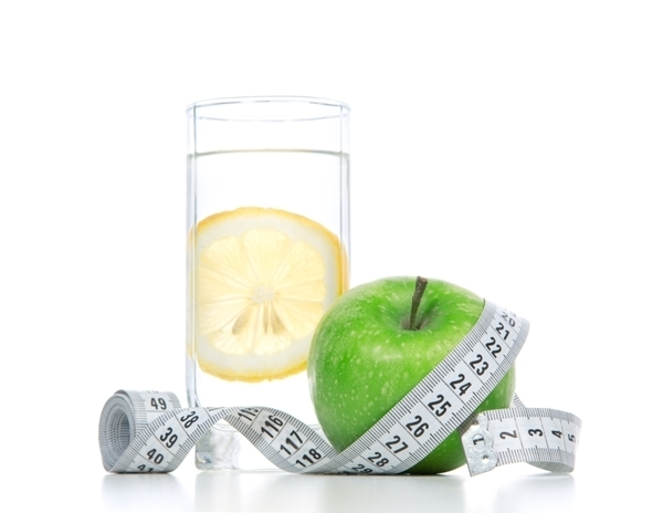 Diet diabetes weight loss concept with tape measure organic green apple and glass of drinking water with lemon on a white background. Focus on water