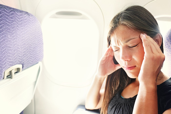 21379787 - fear of flying woman in plane airsick with stress headache and motion sickness or airsickness. person in airplane with aerophobia scared of flying being afraid while sitting in airplane seat.
