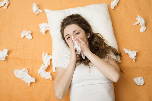 26863853 - sick woman lying in bed with cold and flu  she is blowing nose