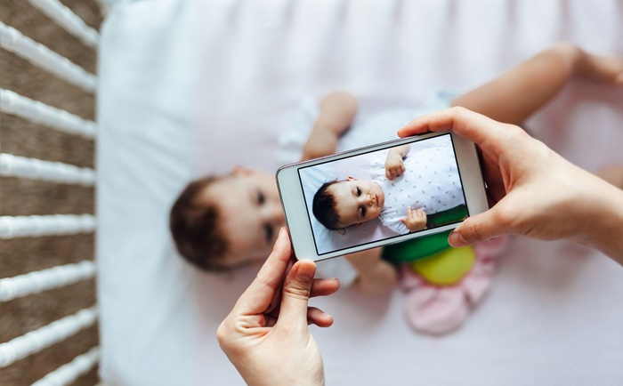 55094683 - happy mother taking a picture of her baby girl in crib with smart phone